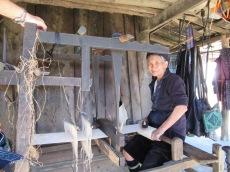 Une femme installée au métier à tisser pour les vêtements traditionnels.