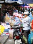 Plusieurs font leurs courses en moto malgré l'espace réduit entre les étals du marché, Chau Doc, Vietnam