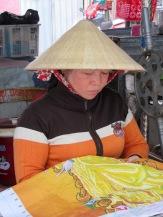 Un petit point de broderie en attendant les clients? Pourquoi pas. Marché de Chau Doc, Vietnam
