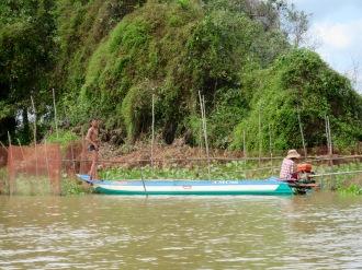 Des pêcheurs s'affairent à réparer une clôture sur un canal menant vers Battambang, Cambodge