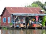 Une petite famille nous salue de son magasin général, Tonlé Sap, Cambodge