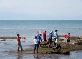 Des enfants s'amusent à faire voler leurs cerfs-volants pendant que des adultes transportent une cage contenant des crabes, Kep, Cambodge