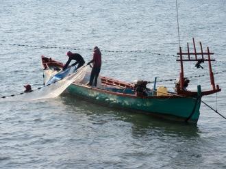 Des pêcheurs retirent leur filet de l'eau, Kep, Cambodge