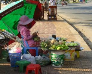 Une marchande attend les clients avec son cellulaire à la main, Kep, Cambodge