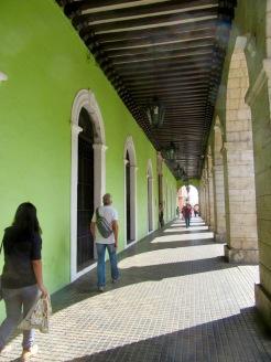 Le passage sous les arcades des édifices patrimoniaux fait partie des incontournables, au bout celui-ci, le Palacio del Gobierno. La visite en vaut la peine. Mérida, Yucatán, Mexique.