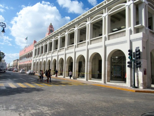 L'édifice rose accueille les danses traditionnelles devant ses arcades. L'édifice blanc abrite des commerces au rez-de-chaussée dont une librairie. Mérida, Yucatán, Mexico.