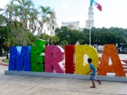Des enfants s'amusent dans le parc et courent autour des fameuses lettres où les gens aiment se faire photographier. Mérida, Yucatán, Mexique.
