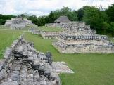 Restes des plateformes sur lesquelles étaient construits les édifices de la ville fortifiée de Mayapan. En arrière-plan, certains vestiges sont protégés des intempéries par un toit en palapa. Yucatán, Mexique.