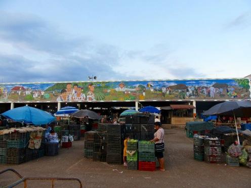 Une grande fresque orne la corniche du marché d'Oxkutzcab. Tout près, sous le parasol bleu, des femmes font une pause. Elles portent les robes traditionnelles de la région. Yucatán, Mexique.