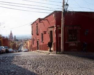 Intersection Salida Real a Queretaro et Correo, juste avant qu'elle ne devienne le Callejón Santo Domingo. Ce n'est pas fini, il faut encore monter pour se rendre où nous habitons. Derrière nous: la Parroquia, le Centro de San Miguel de Allende et ses lacs au loin. Guanajuato, Mexique.