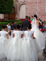La future mariée et ses demoiselles d'honneur traversent le jardin avant d'entrer à l'église San Francisco, San Miguel de Allende, Guanajuato, Mexique.