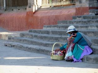 Assise sur le parvis de la Parroquia, une marchande de poupées prend une petite pause pour remettre de l'ordre dans son panier, San Miguel de Allende, Guanajuato, Mexique.