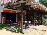Comme la plupart des commerces et des maisons, le Thongs Café est construit sur le sable. Ses chaises peintes et les coussins assortis, rendent le café très accueillant. Sur la terrasse à droite, des balançoires remplacent les chaises. C'est joli! Hopkins, Stann Creek District, Belize.