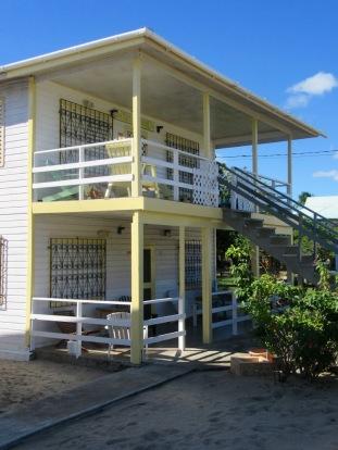 Certaines maisons de bois sont coquettes et très bien entretenues. Devant celle-ci, deux iguanes ont élu domicile sous le trottoir. Placencia, Stann Creek District, Belize.