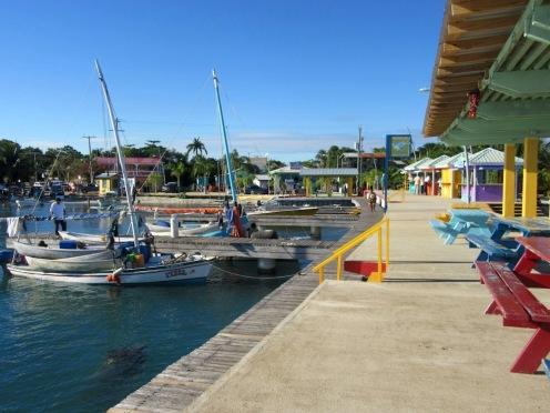 De petits voiliers sont amarrés long du quai de Placencia. Je me demande bien pourquoi ils transportent un chargement de petites embarcations! Stann Creek District, Belize.