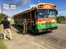 Les autobus du Belize sont des anciens autobus scolaires. Ici, le préposé vient de sortir les bagages d'un passager. Nous attendons sa permission avant d'entrer afin de laisser le passage à ceux qui sortent. Toledo District, Belize.