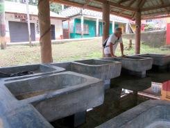 L'installation de ce lavoir est très efficace. Les vêtements sont lavés dans une des cuves de béton alors que l'eau claire du fond du lavoir est recueillie à l'aide d'un récipient. Livingston, Guatemala.