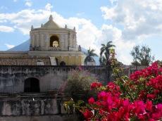 Du deuxième étage des ruines du couvent Nuestra Siñora De la Merced, nous apercevons l'église du même nom et l'un des trois volcans qui entourent la ville. Antigua, Guatemala.