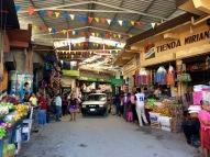 Les autobus et les microbus passent à travers les étals du marché à Flores, Petén, Guatemala.