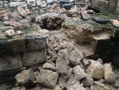 Le gardien du site nous explique qu'ils ne doivent pas essayer de réparer les dégâts des pilleurs, mais plutôt attendre la venue des archéologues afin qu'ils puissent numéroter les pierres avant d'amorcer les travaux et de tout replacer dans le bon ordre. (Photo de Robert) Aguateca, Petén, Guatemala.