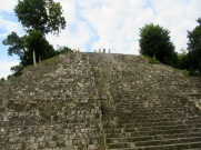 Je reste les pieds sur le sol, au milieu de l'Acropolis Norte à observer mon amoureux devenu si petit en haut de ce temple. Cela me permet d'apprécier la hauteur de la structure qui se dresse devant moi. Yaxhá, Petén, Guatemala.