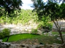 Un sacbé nous mène vers le Cenote Sagrada, le cénote principal de Chichen Itzà. Ses parois sont d'environ 27 mètres. Tout près, les restes d'un petit temple sont visibles. Yucatán, Mexique.