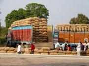 Des chargement de sacs de riz sont acheminés à la gare. Inde.