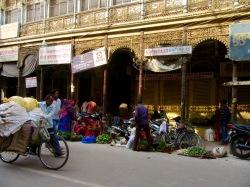 Un marché a élu domicile devant une maison ancestrale le long d'une rue achalandée, Varanasi, Inde.