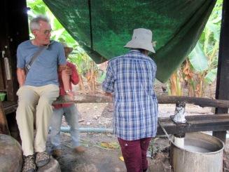 Mon amoureux s'est offert pour aider à presser la pâte de riz qui tombe dans la marmite remplie d'eau. Même avec l'effet de levier il n'est pas assez lourd! Sokcheat doit ajouter du poids. Chhlong, Cambodge.