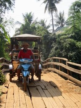 Ce pont de bois craquait de toutes ses planches, mais Sokcheat l'a emprunté sans aucune crainte. Kratie, Cambodge.