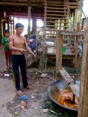 Le sirop de palme est bouilli sur un feu de bois. Lorsqu'il est suffisamment réduit, il est baratté à l'aide d'un dispositif artisanal et devient du sucre. Kratie, Cambodge.