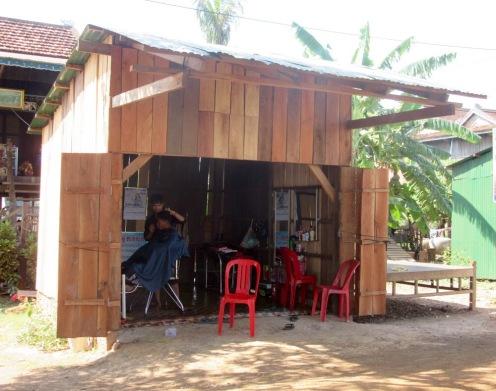 Un coquet salon de coiffure pour hommes, au bord de la route. Kratie, Cambodge.