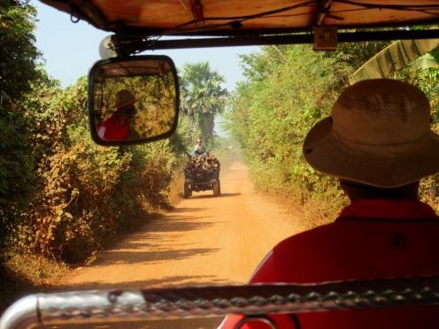 Les rencontres sur la route de terre orangée soulèvent beaucoup de poussière. Sokcheat porte un masque pour protéger ses poumons. Kratie, Cambodge.