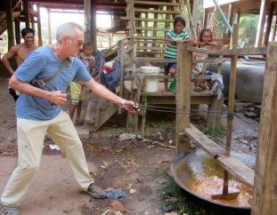 Le barattage du sirop de palme demande force et dextérité. Mon amoureux s'en tire très bien! Kratie, Cambodge.