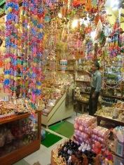 Un marchand prend une pause dans son magasin tout en couleurs situé dans une ruelle du vieux quartier Chowk, Varanasi, Inde.
