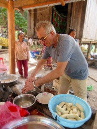 Robert prépare une banane qui sera trempée dans une pâte puis frite dans une grande marmite. Kratie, Cambodge.
