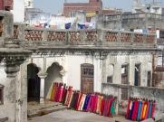 Un marchand a étalé ses rouleaux de tissus chatoyants sur le toit, Varanasi, Inde.