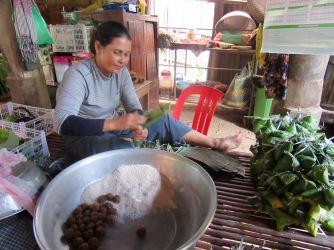 Cette femme prépare des collations avec du riz et du sucre de palme enveloppés dans des feuilles de bananier qu'elle vendra ensuite à l'entrée du temple tout près. Chhlong, Cambodge.