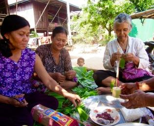 Ces femmes préparent des décorations pour une cérémonie religieuse suite à la construction de la maison voisine. Les bonzes viendront pour la célébration. Kratie, Cambodge.