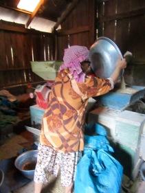 Dans sa petite fabrique sous sa maison, cette femme traite les grains de riz pour enlever leur enveloppe brune. Les grains proviennent des habitants des environs qui ont fait sécher leur production au soleil, sur une grande bâche, devant leur maison. Chhlong, Cambodge.