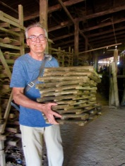 Les tuiles humides sont déposées sur un petit support de bois et placées sur des tablettes pour le séchage. Kratie, Cambodge.