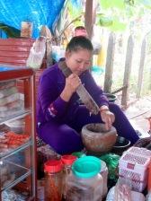 Assise sur une grande structure basse qui ressemble à une énorme table, cette jeune femme prépare une sauce pour accompagner ses plats, Kratie, Cambodge.