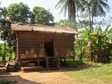 La pauvreté a plusieurs visages. Certaines maisons sont construites avec des matériaux empruntés à la nature qui ne résistent pas aux intempéries. La femme qui habite cette maison a tenu à ce que nous la prenions en photo. Kratie, Cambodge.