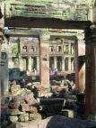 Un édifice de deux étages avec des colonnes rondes est visible à travers une ouverture aux pierres rosées à Preah Khan, Siem Reap, Cambodge.