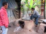 Les collations sont bouillies dans une grande marmite jusqu'à ce que ce riz soit tendre. Les fours et la grande table basse où elle s'asseoit pour travailler sont situés sous sa maison sur pilotis. L'air y circule bien et c'est confortable. Chhlong, Cambodge.
