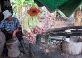 Le poids de deux femmes est nécessaire pour presser la pâte de riz pour en faire des nouilles. Chhlong, Cambodge.