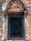 Un Bouddha aperçu par une fenêtre attire notre attention, allons voir de plus près. Wat Samanakottaram, Ayutthaya, Thailande.