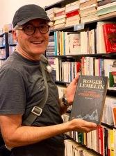 Mon amoureux heureux de sa trouvaille dans une librairie de livres usagés: une œuvre de Roger Lemelin, en bon état. Phnom Penh, Cambodge.