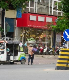 Pas facile de traverser une rue passante avec un enfant dans les bras et son commerce sur la tête. Phnom Penh, Cambodge.
