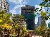 Alors que j'écris, confortablement installée à la terrasse de l'hôtel, devant notre chambre au 5e étage, un mouvement attire mon attention. Un homme travaille debout sur un échafaud presque en haut de l'immense en construction devant moi. Pouvez-vous le voir? Phnom Penh, Cambodge.